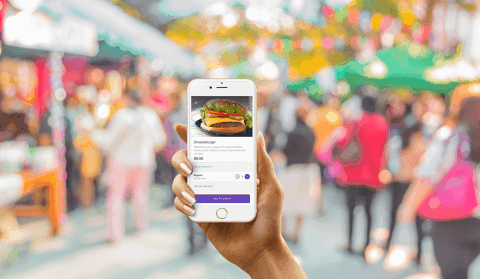 Hand holding smartphone showing mobile food ordering application