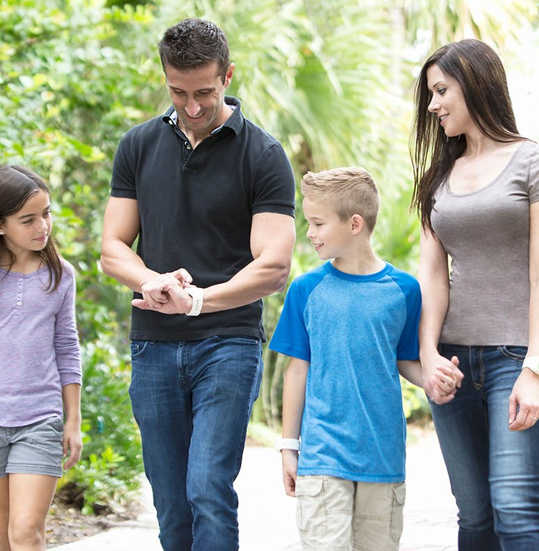 Family of four using a virtual queuing device with the man looking down at the accesso Prism band and the rest of the family walking together and watching him