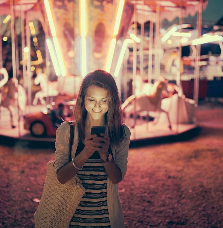 Woman at a theme park standing in front of a carousel at night looking at her mobile app